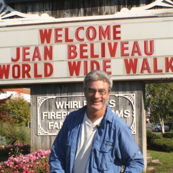 Jean-Beliveau-poses-in-front-of-a-welcome-sign-in-Ontario
